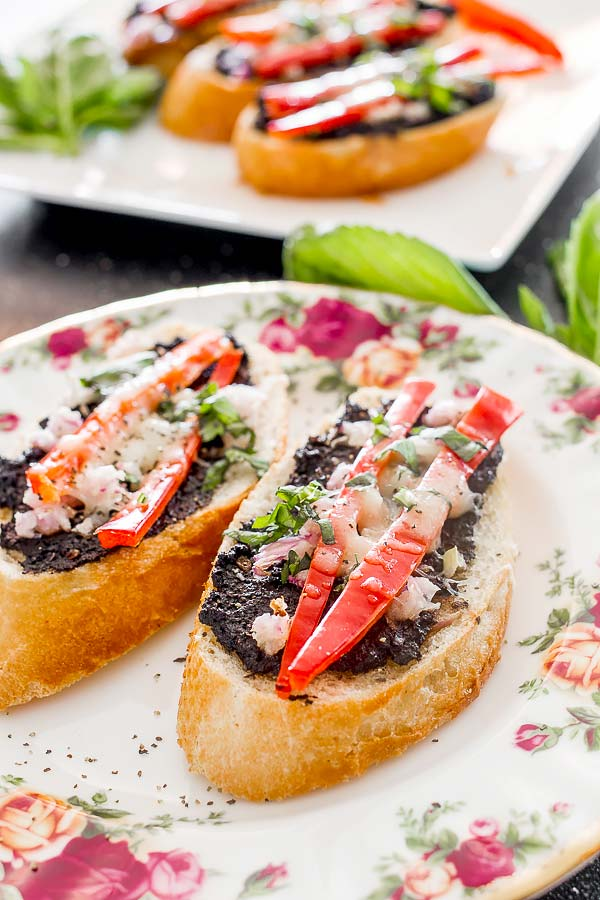 Delicious appetizers featuring a home-made olive spread topped with shredded cheese and basil